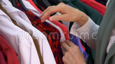 Woman hands searching casual blouse in boutique. Female shopping fashion clothes in clothing store. Customer fingers choosing fabric. Casual style. Trendy wear stock video