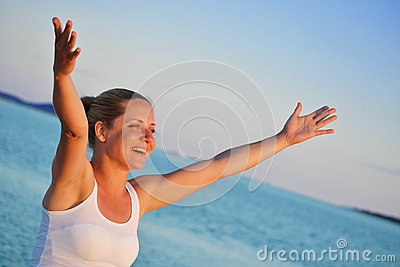 Woman with hands up expressing joy on the beach