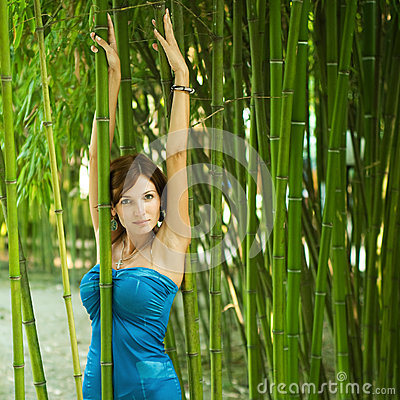 Woman with hands up in a green bamboo garden