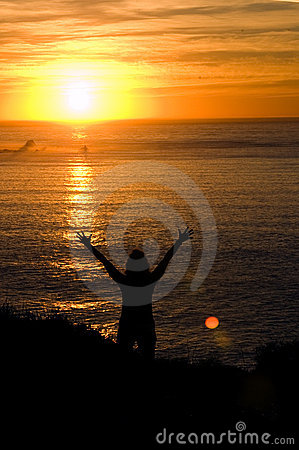 Woman with hands upheld at sunset
