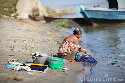Woman handwashing clothes at the riverside in Myan Editorial Photo