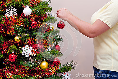 Woman hanging a baubel on a Christmas tree