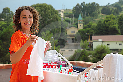 Woman hangs clean wear on balcony