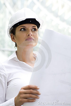 Woman in hardhat holding blueprints