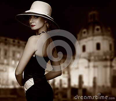 Woman in hat against night city view