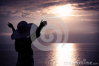 Woman in Hat with Raised Hands Looking at Sunset