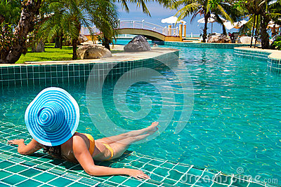 Woman in hat relaxing at tropical swimming pool