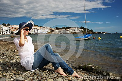Woman in hat sitting on a beach