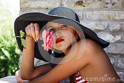 Woman in hat smell flower