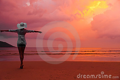 Woman in hat standing on wet sand on beach