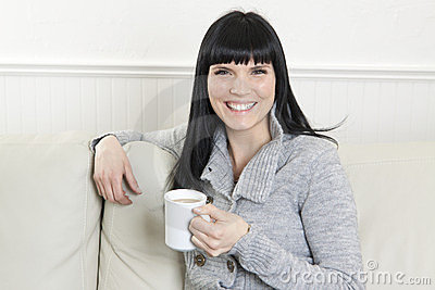 Woman having a coffee and relaxing at home