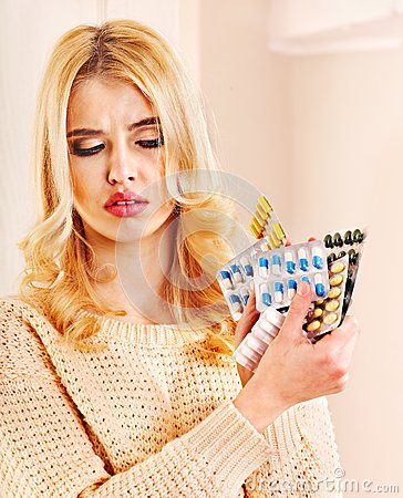 Woman having flu takes pills.
