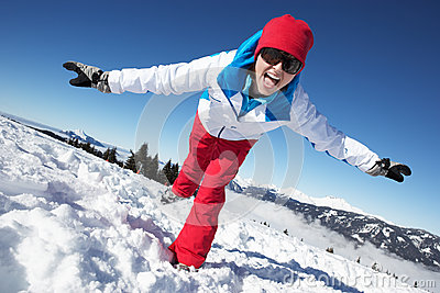 Woman Having Fun On Ski Holiday In Mountains