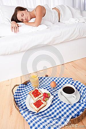 Woman having homemade breakfast lying in bed
