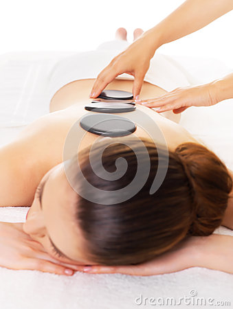 Woman having hot stone massage in spa salon.