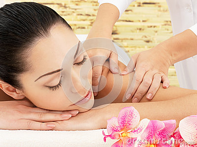 Woman having massage of shoulder in spa salon