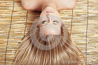 Woman head with makeup on bamboo mat
