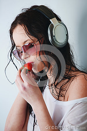 Woman in headphones eating strawberry