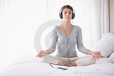 Woman with headphones in lotus position on bed