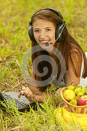 Woman with headset lie on grass