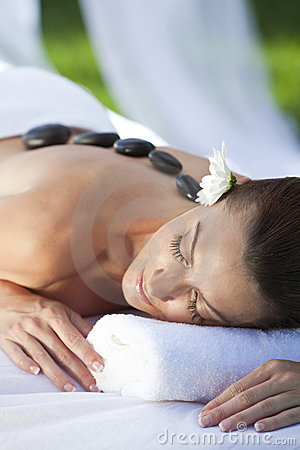 Woman At Health Spa Having Hot Stone Treatment