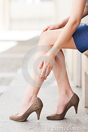 Woman in heels massaging tired legs
