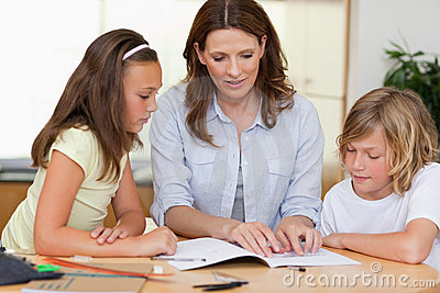 Woman helping children with homework