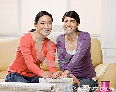 Woman helping friend wrap birthday gift