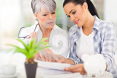 Woman helping mother paying bills