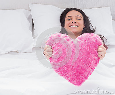 Woman in her bed holding a fluffy heart cushion