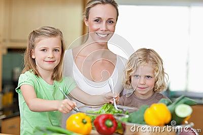 Woman with her children preparing salad