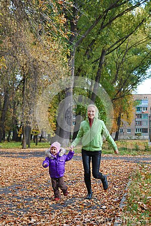 Woman  with her daughter in the autumn park