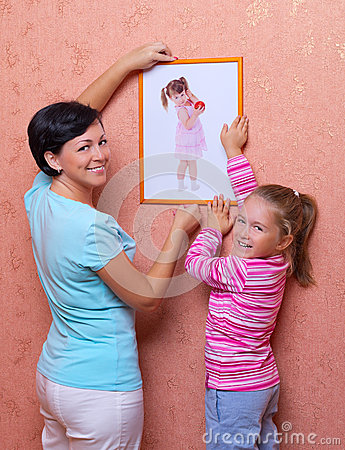 Woman and her daughter hanging up photo