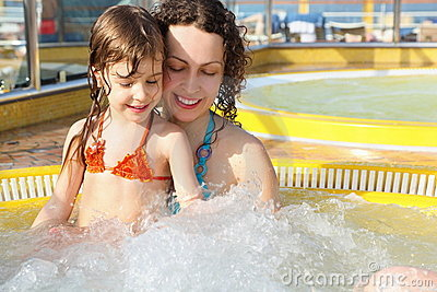 Woman with her daughter is relaxing in hot tub