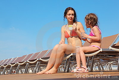 Woman with her daughter sitting on chaise longues