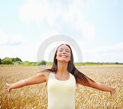 Woman with her hands raised out in the open farm