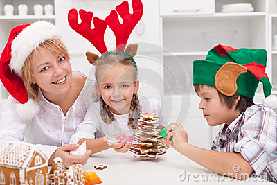 Woman and her kids decorating christmas cookies