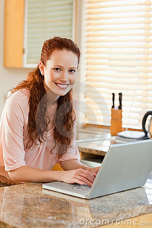 Woman with her laptop next to the kitchen counter
