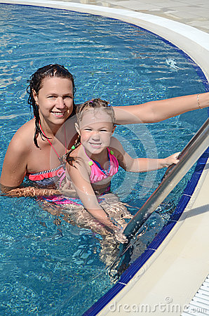 Woman and her little cute daughter have a fun in pool