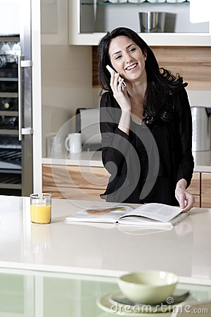 Woman on her mobile in a kitchen