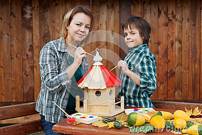 Woman and her son painting a bird house