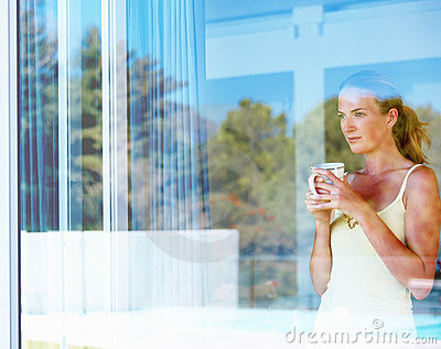Woman at her window having tea and thining