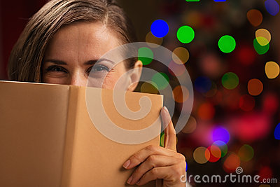 Woman hiding behind book near Christmas lights