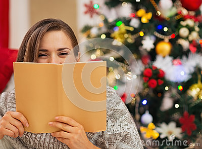 Woman hiding behind book near Christmas tree