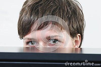 Woman hiding behind desk