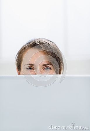Woman hiding behind laptop