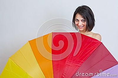 Woman hiding over colorful umbrella