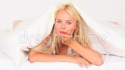 woman hiding under her sheet Stock Photo