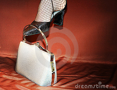 Woman with high heel k shoes and silver purse