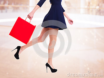 Woman in high heels with red shopping bag.